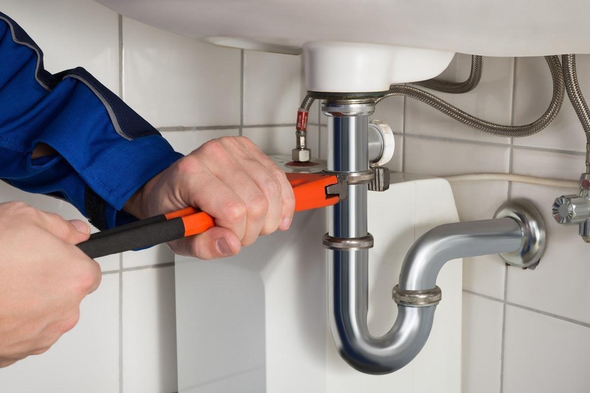 dokręcanie rury kluczem hydraulicznym przy umywalce